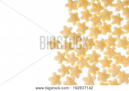 Decorative border of yellow stars corn flakes isolated on white background. Copy space cereals texture.