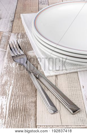 A knife and fork with plates and napkin on a rustic wooden table