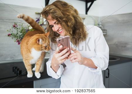Woman in a white man's shirt is standing in the kitchen. A girl shows the cat a smartphone screen and smiles. Cat is looking at the phone.