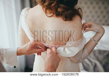 A man undresses a woman. Wedding preparations