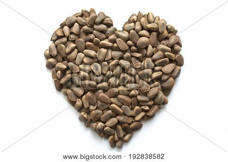 Heart shaped brown Korean cedar nuts isolated on white background