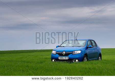 Gomel, Belarus - May 24, 2017: Reno Logan Blue Car Is Parked On The Green Field.