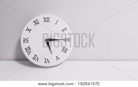 Closeup white clock for decorate show a quarter past five o'clock or 5:15 p.m. on white wood desk and wallpaper textured background in black and white tone with copy space