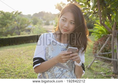 asian younger woman with smartphone in hand happiness thinking relaxing outdoor