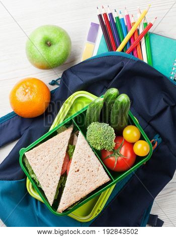 Lunch box with vegetables and sandwich on wooden table. Kids take away food box and school supplies. Top view