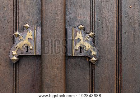 Old wooden oak arched gothic church doorway with black wrought iron hinges.