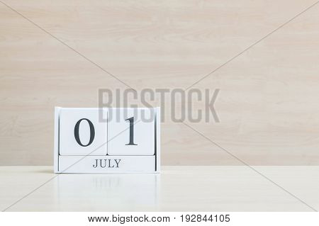 Closeup surface white wooden calendar with black 1 july word on blurred brown wood desk and wood wall textured background with copy space selective focus at the calendar