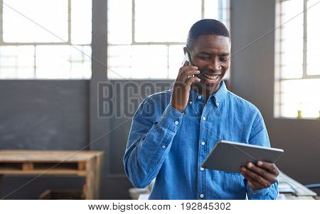 Smiling young African businessman standing in a large modern office working on a digital tablet and talking on a cellphone