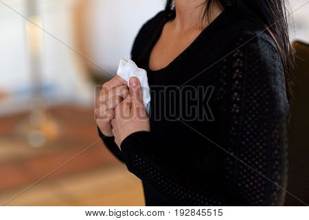 people, grief and mourning concept - close up of woman with wipe at funeral in church