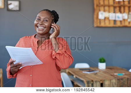 Portrait of a casually dressed young African businesswoman reading paperwork and talking on a cellphone while standing in large a modern office