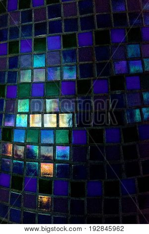 Wall with small mosaic tiles texture in gloss grey black green bue color. It's not a pattern it seems more like abstract view