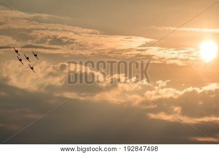 Acrobatic planes doing acrobatics at an Airshow flying at sunset