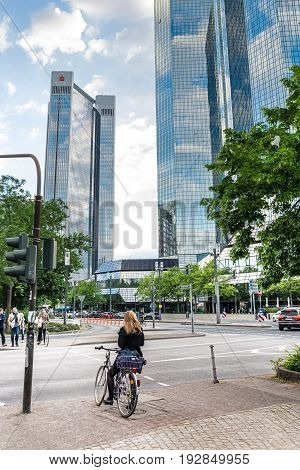 Woman On A Bicycle With Tall Office Buildings In The Background