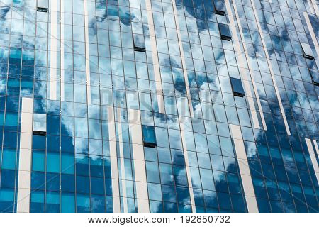 Futuristic industrial structure with reflection of cloudy sky