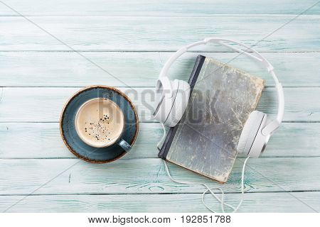 Audio book concept. Headphones, coffee and book over wooden table. Top view with space for your text