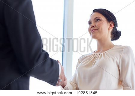 business, partnership and cooperation concept - smiling people shaking hands at office