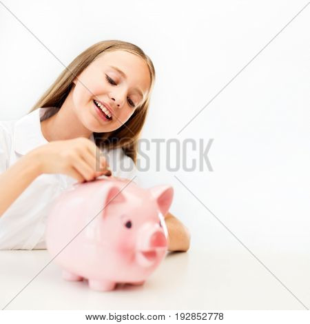 people, saving and finances concept - happy smiling girl putting coin into piggy bank