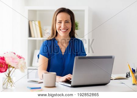 business, people and technology concept - happy smiling woman with laptop computer working at home or office