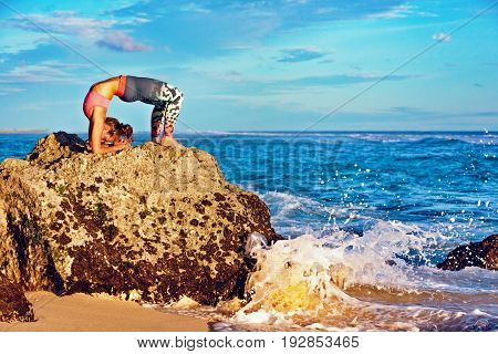Meditation on sea surf with splashes background. Active woman on beach rock in yoga pose to keep fit and health. Healthy lifestyle fitness training sport activity on summer family holiday