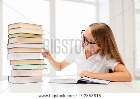 education, school and people concept - student girl in eyeglasses with pile of books sitting at table