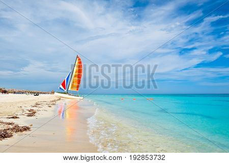 Sunny day at Varadero beach on the island of Cuba with a colorful sailboat
