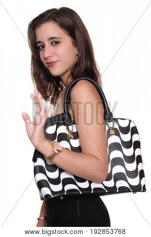 Beautiful teenage girl wearing a black dress and a purse  smiling and waving goodbye - Isolated on white