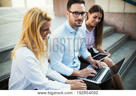 Three young smiling cheerful colleagues working together on laptop