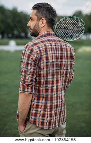 Handsome Caucasian Man Holding Badminton Racquet And Standing On Green Field