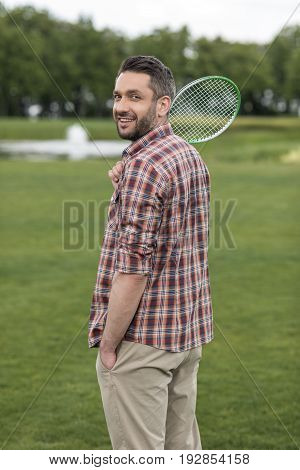 Bearded Man In Checkered Shirt Holding Badminton Racquet And Smiling At Camera