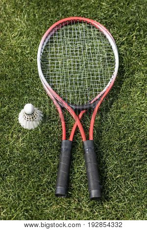 Top View Of Badminton Rackets With Shuttlecock On Grass Field