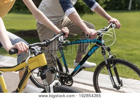 Cropped Shot Of Young Casual Couple Riding On Bicycles In Park At Daytime