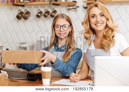 Enjoyable work. Pleasant upbeat girl handing a box with an order to the customer outside the camera view while her mother making notes in a report, both of them smiling at the camera