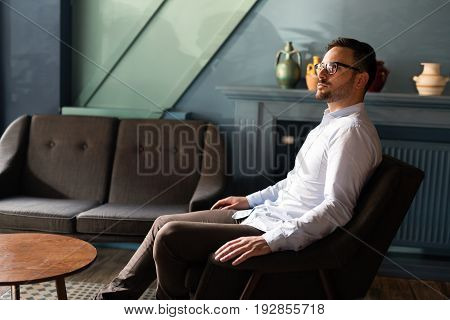 Portait of young handsome businessman in glasses sitting