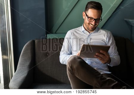 Portait of businessman in glasses holding tablet indoors