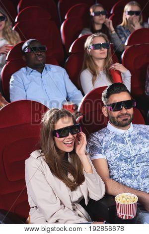 Vertical shot of group of people smiling watching a 3D movie at the movie theatre technology happiness positivity expressive emotions entertaining recreation weekend concept.