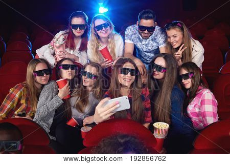 Diverse group of friends wearing 3D glasses relaxing together at the cinema taking a selfie with a smart phone technology gadget connectivity mobility online social friendship entertainment concept.