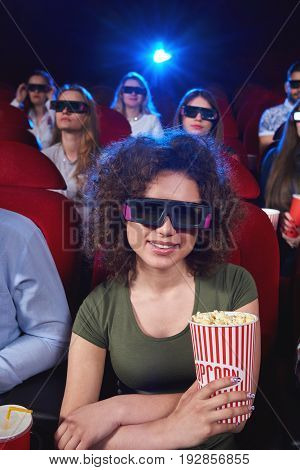Vertical portrait of a beautiful young woman smiling enjoying 3D movie premiere at the cinema holding popcorn sitting relaxed entertaining activity spectator viewer positivity technology.