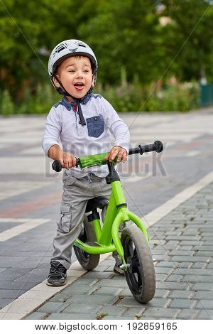 Child boy in white helmet riding on his first bike with a helmet. Bike without pedals. Child learning to ride and balance on his two wheeler bike with no pedals.