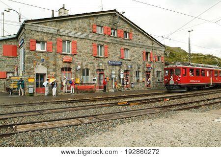 Ospizio Bernina Switzerland - 20 July 2015: People waiting to take the Bernina express train at the station of Ospizio Bernina on the Swiss alps
