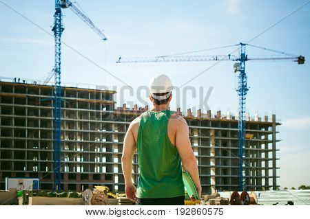 Young Sexy Men Bodybuilder Athlete. Manager Engineer Builder In White Protective Helmet Stands On Ba