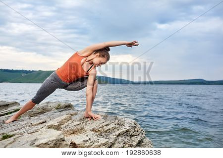 Young woman standing in yoga pose on the big stone near beautiful river. Sporty woman dressed in the sportwear and barefoot. Beautiful landscape like background. Horizontal photo. Concept of the healthy lifestyle.