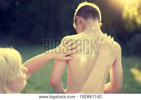 Mother applying sunscreen creme for little son vintage