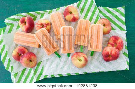 Homemade frozen popsicles with fresh ripe doughnut peaches