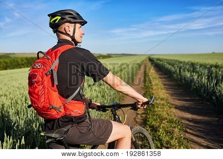 Attractive cyclist standing with mountain bicycle in field with blue sky on a background. Sportsman dressed in the black sportwear, with backpack and helmet. Travel in the countryside. Concept of the healthy and active lifestyle.
