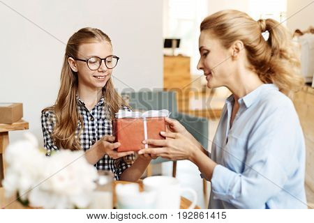 Best wishes. Lovable fair-haired girl receiving a beautifully wrapped birthday present from her mother