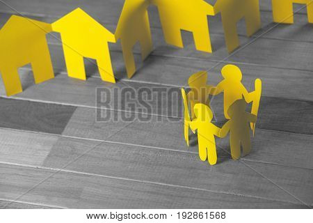 High angle view of paper figures and houses on wooden table