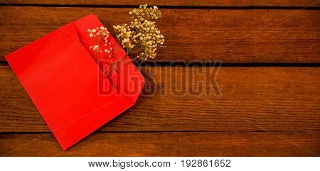 High angle view of white flower in envelope on wooden plank