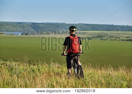 Rear view of the cyclist standing of the hill against beautiful summer landscape. Young sportsman dressed in the black sportwear, with backpack and helmet. Extreme travelling in the countryside. Concept of the healthy and active lifestyle.