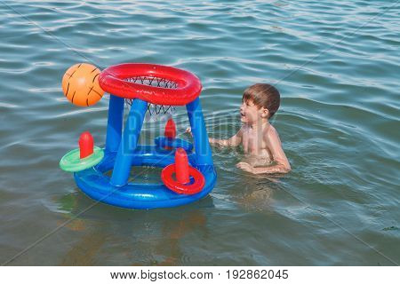 A Boy On The Beach Playing In The Water With An Inflatable Ball. Little Boy Playing Basketball In Th