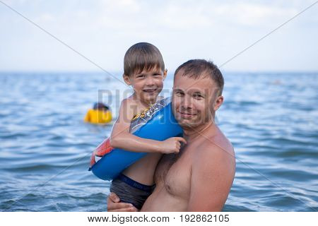 A Little Boy Is Swimming With His Dad In The Sea.